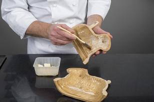 Badigeonner un moule « agneau » en terre cuite avec du beurre